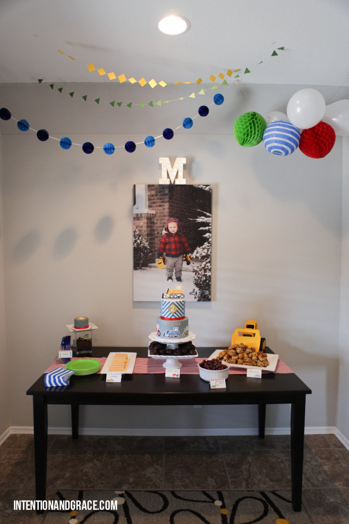 Setting up a birthday party table - banners, food cards, cake, paper balls, balloons, etc. |  intentionandgrace.com
